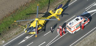 """Symbolfoto zum Beitrag """"Motorroller-Fahrer verursacht schweren Unfall auf der A1"""". Vogelperspektive mit Blick auf eine Straße, auf der ein ADAC-Hubschrauber sowie ein Rettungswagen parken. Sanitäter stehen hinter dem Fahrzeug."""