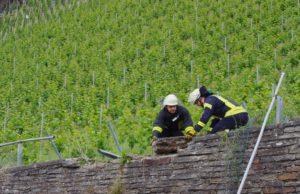 Feuerwehrmänner sicher die Mauer, die von der Raupe beschädigt wurde