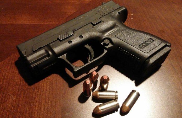 Nahaufnahme einer Pistole mit Munition daneben - liegend auf einem Holztisch.