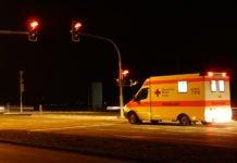 """Symbolbild. Krankenwagen bei Nacht an einer roten Ampel wartend für den Bericht """"Toter Fahrradfahrer im Straßengraben gefunden""""."""
