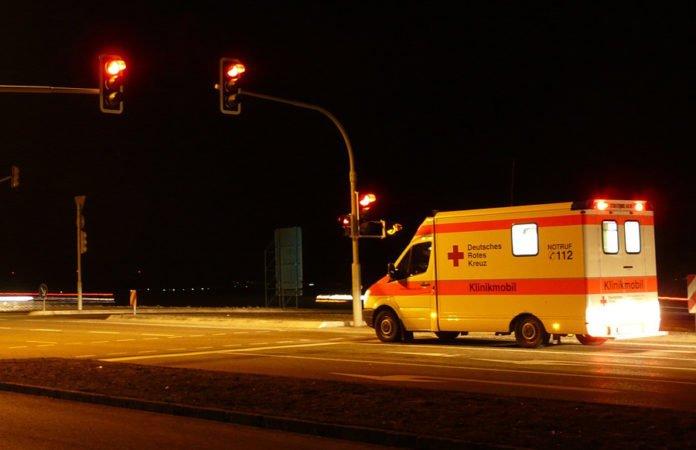 Symbolbild. Krankenwagen bei Nacht an einer roten Ampel wartend für den Bericht