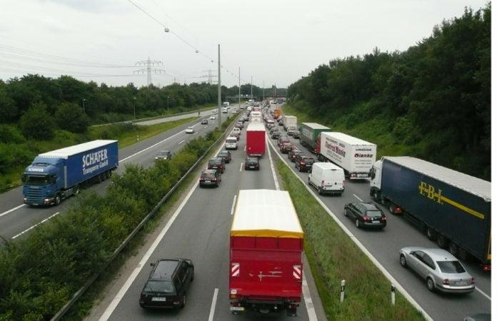 Verkehrende Diesel- und Benzinfahrzeuge auf einer sich stauenden Autobahn.