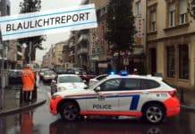 Symbolbild für die Verfolgungsjagd in Luxemburg. Ein Polizeiwagen sperrt eine Straße ab. Es regnet.