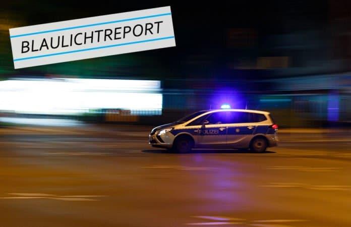 Symbolbild. Ein Polizeiwagen rast mit Blaulicht durch die dunklen Straßen einer Stadt. für den Bericht