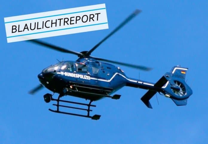 Symbolbild. Nahaufnahme eines fliegenden blauen Polizeihubschraubers vor blauem Hintergrund für den Beitrag