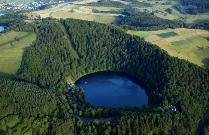 Vogelperspektive auf einen Vulkansee in der Vulkaneifel, der mit viel Wald umrandet ist.