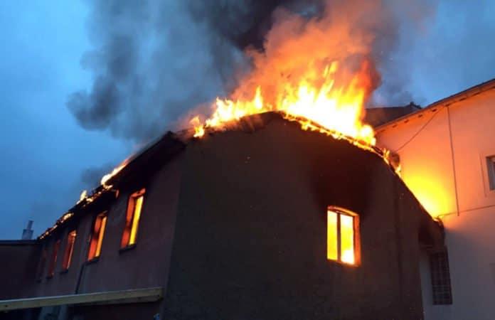 Symbolbild. Ein in Flammen stehendes Haus, bei Dämmerung.