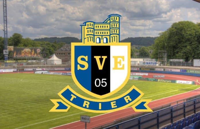 Das Logo vom SV Eintracht Trier 05 e.V. vor dem Hintergrund eines Sportplatzes.