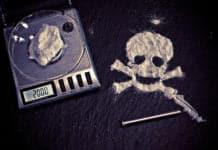 Drogentote. Drogen auf einer Waage und daneben ein Totenkopf.