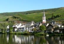 Ein Blick vom See aus zum Ort Zellmosel, wo die Scheiche Häuser kauften. Im Hintergrund sind die grünen Hügel und der blaue Himmel zu sehen.
