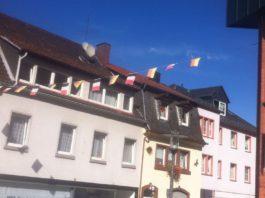 Eine Fahnen-Girlande, die zwischen zwei Häuser über eine Straße gehangen ist.