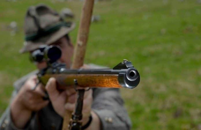 Symbolbild. Nahaufnahme eines Gewehrlaufs, das von einem zielenden Jäger gehalten wird.