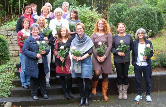 Die Ehrenamtlichen vom Hospizdienst stehen für eine Fotoaufnahme in einer Gruppe, teils auf einer Treppe, mit Blumen zur Auszeichnung in den Händen und freuen sich sehr.