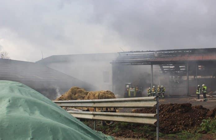 Szene nach dem Großbrand mit Feuerwehrleuten, die vor und in der Stallung im Rauch stehen.