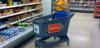 Frau steht vor Regal im Supermarkt