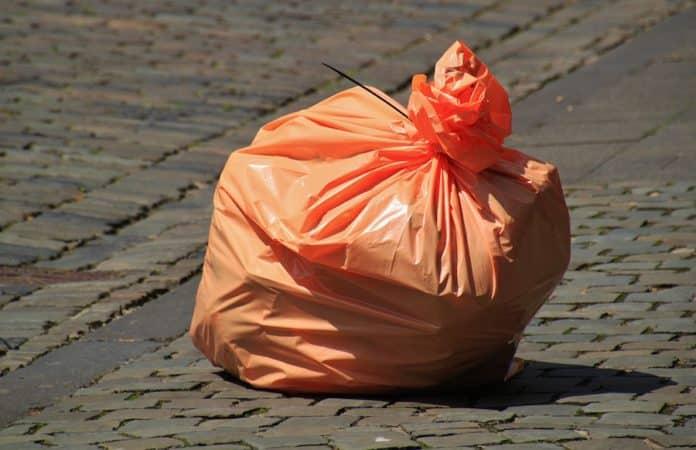 Symbolbild für das Sexspielzeug im Müllsack. Ein Orangener Plastiksack steht auf einem Weg aus Kopfsteinpflaster.