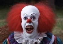 Ein Clown mit wilden roten Haaren und Halbglatze, der seine grässlichen Zähne mit weit geöffneten Mund zeigt.