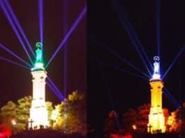 Die Mariensäule erstrahlt unter Beleuchtungen in rot, gelb, blau und grün im Nachthimmel.