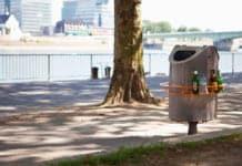 """Ein orangener Pfandring ist um einen Mülleimer an einem Fußweg """"geschnallt""""."""