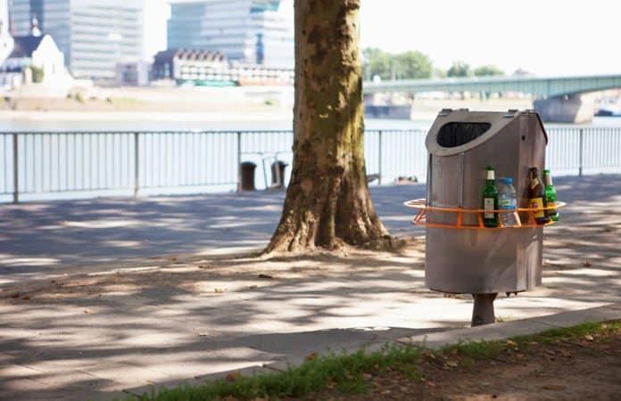 Ein orangener Pfandring ist um einen Mülleimer an einem Fußweg