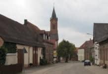 Eine Straße zur Reichenberger Kirche, die von einer Fliegenplage heimgesucht wurde. Rechts und links von ihr stehen Häuser und der Himmel ist bedeckt.