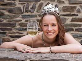 Deutsche Weinkönigin aus Mehring, Lena Endesfelder, ist mit einem gefüllten Weißweinglas in der Hand und einer Krone im Haar zu sehen. Sie lehnt mit beiden Armen vor sich geknickt auf einer Felsmauer und lacht fröhlich.
