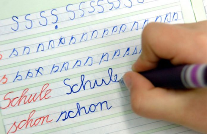 n einer Schule schreibt ein Mädchen im Unterricht das Wort «Schule» in ihr Heft