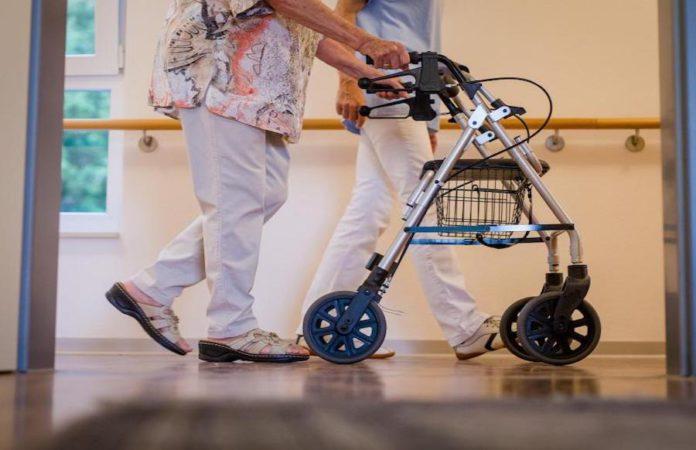 Pflegerin und Ältere mit Rollator