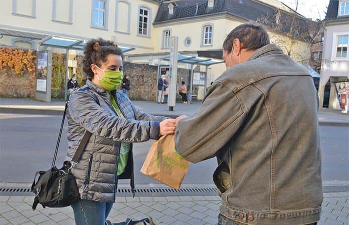 Esther Pickmann überreicht ein Hygiene-Set an einen Obdachlosen in Trier